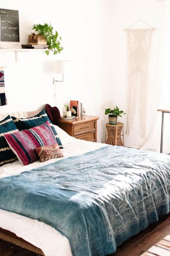 un boho incontra una camera da letto moderna della metà del secolo con ricchi mobili colorati, un appeso in macramè e piante in vaso