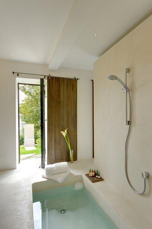 un bagno semplice e nautico in cemento e pietra, con vasca incassata e porta scorrevole per una boccata d'aria fresca