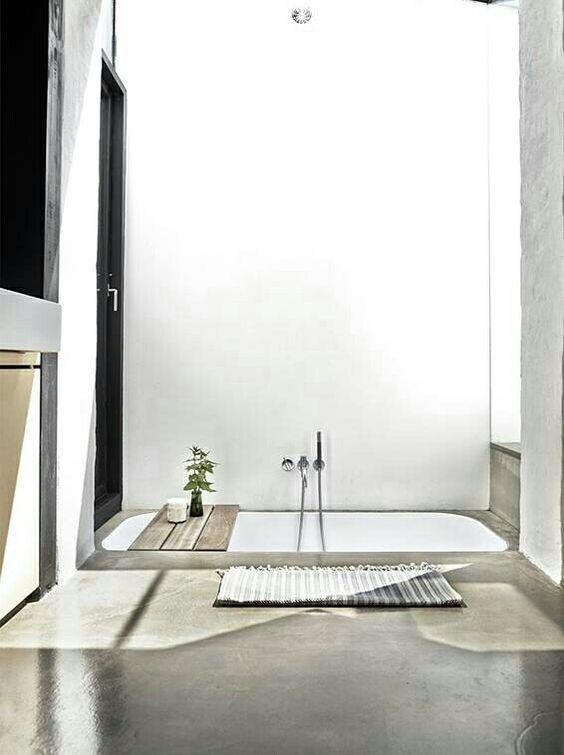 un bagno minimalista fatto in cemento e con una vasca incassata bianca è molto semplice, casual e senza problemi