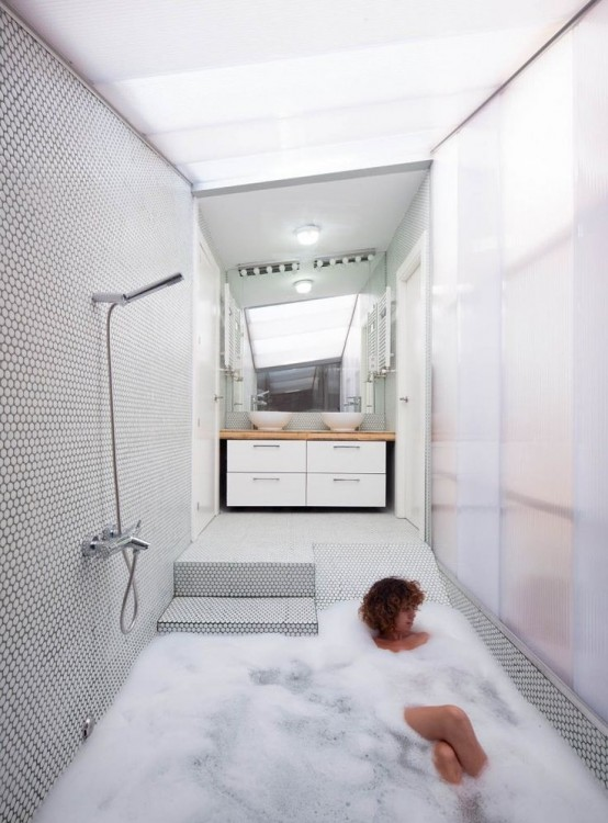 un bagno minimalista con vasca incassata che si abbina allo spazio doccia per ingrandirne il quadrato