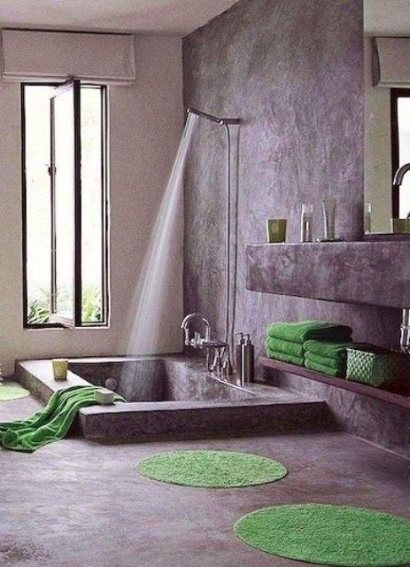 un bagno wabi-sabi con mensole e una vanità di cemento e una vasca da bagno incassata più una finestra a bilico per far entrare un po 'di luce