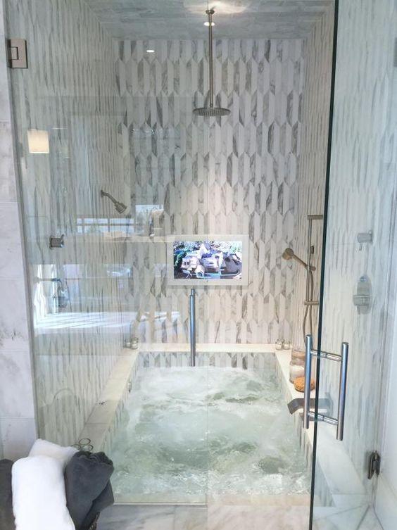 una vasca incassata combinata con uno spazio doccia e rivestita con piastrelle neutre e accattivanti è molto confortevole e poco ingombrante