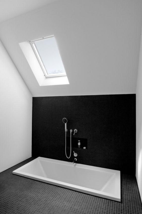 un bagno minimal monocromatico in bianco e nero, con lucernari e una vasca incassata è uno spazio molto semplice ed elegante