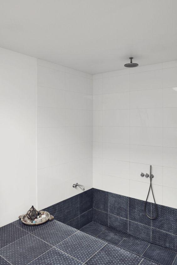 un bagno minimalista con piastrelle bianche, piastrelle grigie sul pavimento e nella vasca incassata è uno spazio fresco