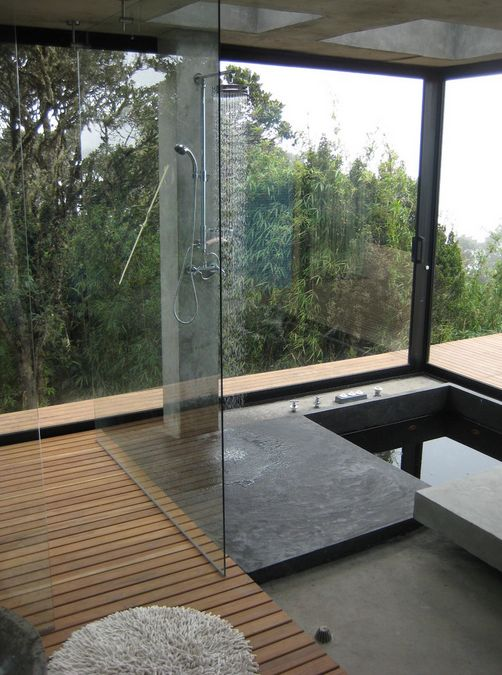 un bagno minimalista con un ponte in legno, uno spazio doccia in cemento e una vasca incassata più una vista panoramica