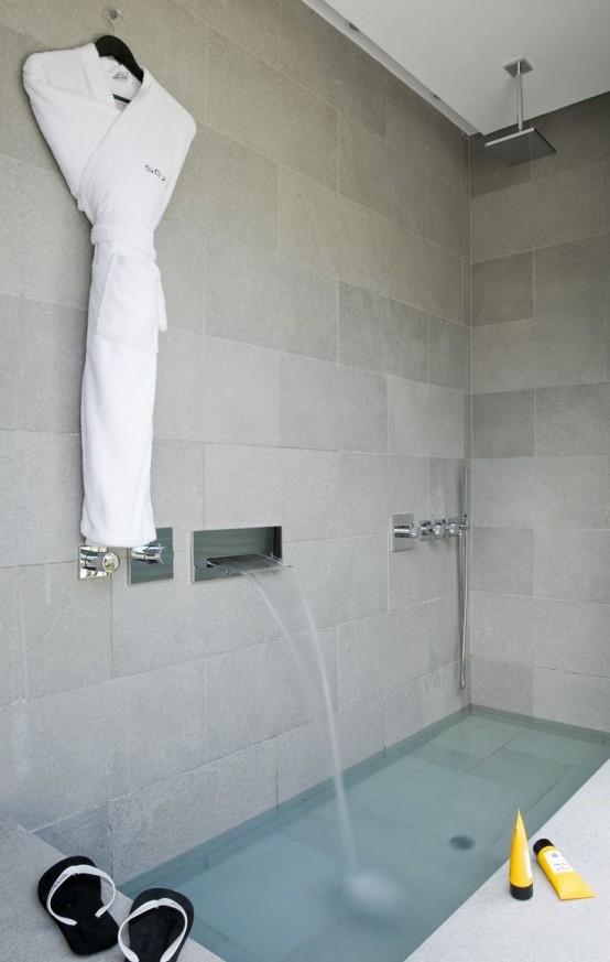 un bagno moderno fatto con piastrelle in pietra e una vasca da bagno incassata più una cascata sembra molto rilassante e rilassante