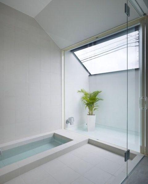 un bagno minimalista con un lucernario, una vasca incassata, uno spazio doccia e una pianta in vaso è rivestito con piastrelle neutre