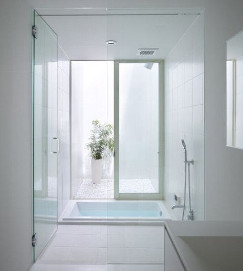 un bagno bianco pulito con una vasca incassata, un lucernario, piante in vaso e un lavandino è molto minimale e semplice