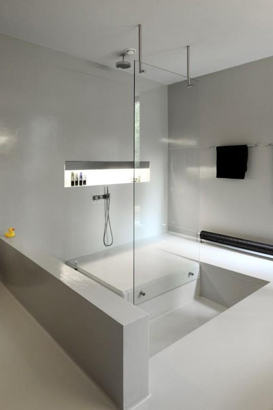 un bagno bianco minimalista con uno spazio doccia e una vasca incassata sembra tutto elegante e chic