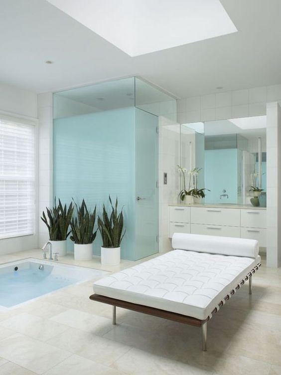 un bagno moderno in bianco e azzurro, con una vasca da bagno incassata e un divano in pelle più piante in vaso per un'atmosfera all'aria aperta