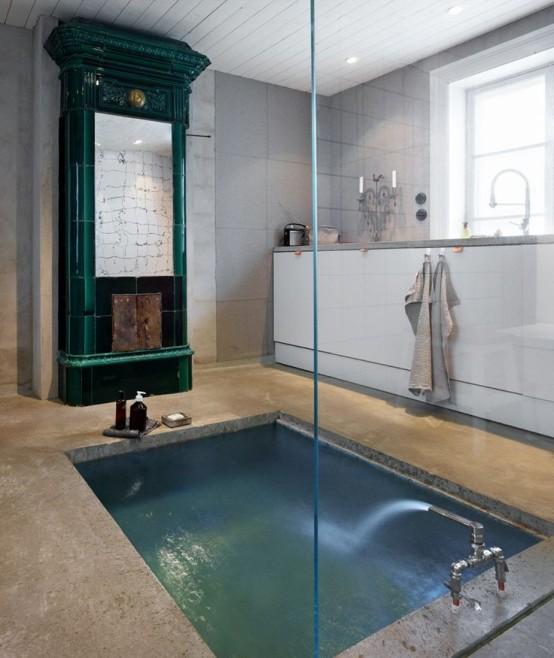 un bagno eclettico con un focolare verde, una vasca incassata in cemento e una consolle bianca