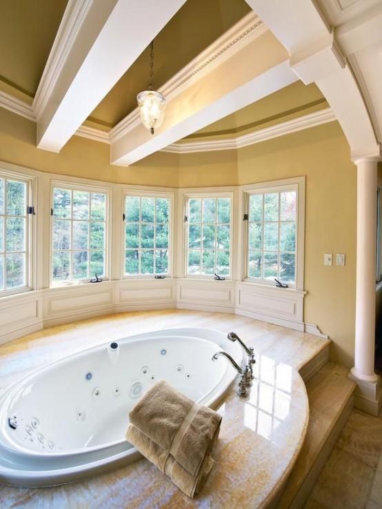 un bagno ampio e accogliente con tante finestre e travi a vista sul soffitto, con una grande vasca ovale più un terrazzo in pietra intorno