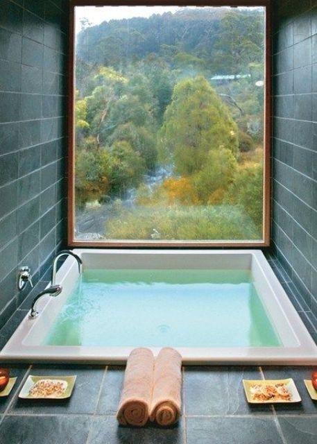 un bagno piastrellato grigio con una finestra panoramica per una vista e una vasca incassata per rilassarsi il più possibile