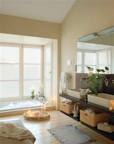 un bagno accogliente e neutro con una vasca incassata, un pavimento in legno, fiori e candele in vassoi più un grande specchio