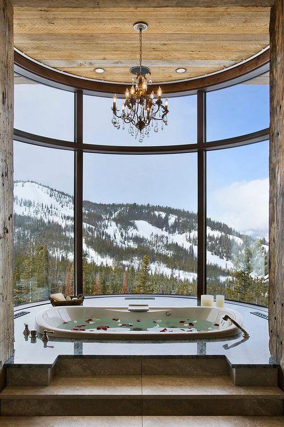 uno splendido bagno con vista panoramica, una vasca da bagno incassata, un lampadario, candele è uno spazio fantastico per godersi il tempo del bagno