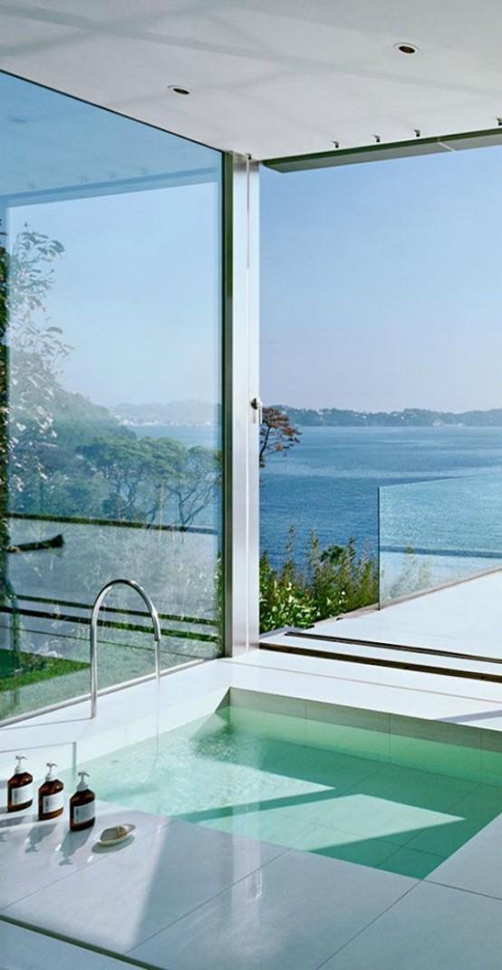 un bagno minimalista tutto vetrato, con vista, con sole e aria, con una vasca incassata che prende il massimo da questi punti di vista
