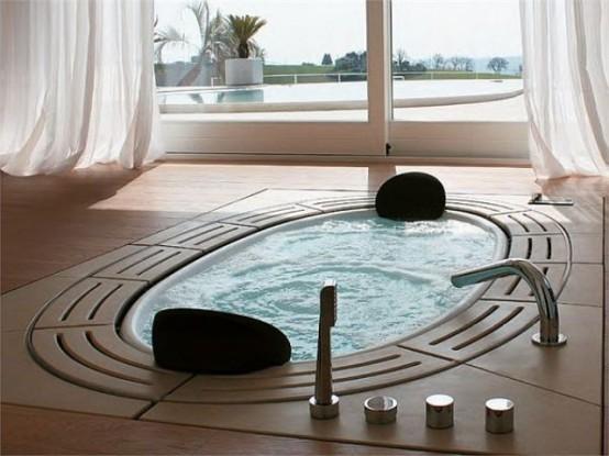 una vasca ovale incassata con piastrelle intorno più un ingresso alla terrazza per riempire lo spazio di luce e aria
