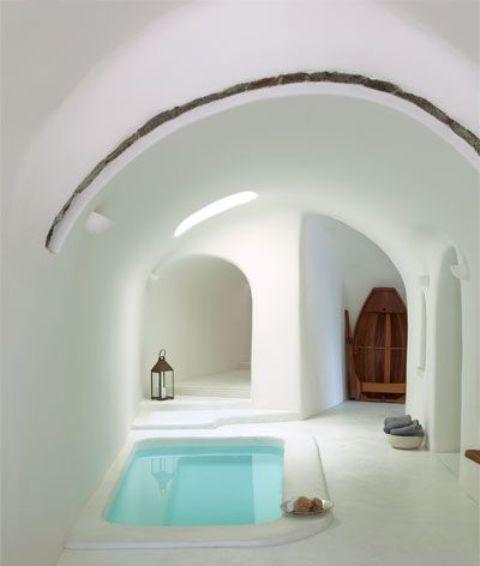 un bagno bianco minimale con un soffitto ad arco più una vasca da bagno incassata, lanterne e spugne intorno