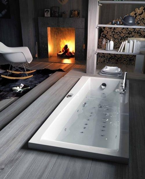 una vasca da bagno incassata con un ponte proprio nella camera da letto con un camino, sembra molto naturale e molto rilassante e piacevole