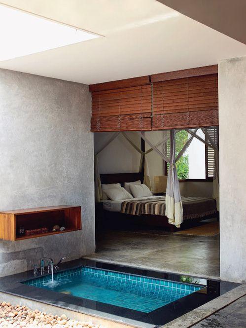 una vasca incassata con piastrelle all'interno e pietra intorno, con sfumature che la separano dalla camera da letto