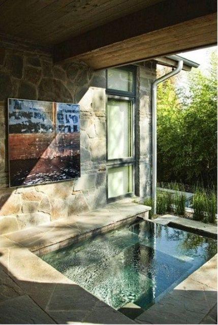 un bagno interno-esterno con vasca o piscina incassata, realizzato con pietra e piastrelle più il sole proveniente dall'esterno