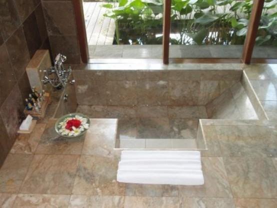 un bagno dall'aspetto naturale con piastrelle in pietra neutra e una vasca incassata con gradini e una parete vetrata con vista