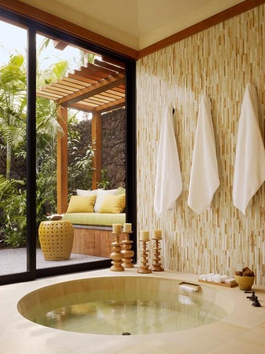 un bagno tropicale fatto in colori neutri, con una vasca da bagno rotonda incassata e porte scorrevoli sul giardino per una vista e più sole