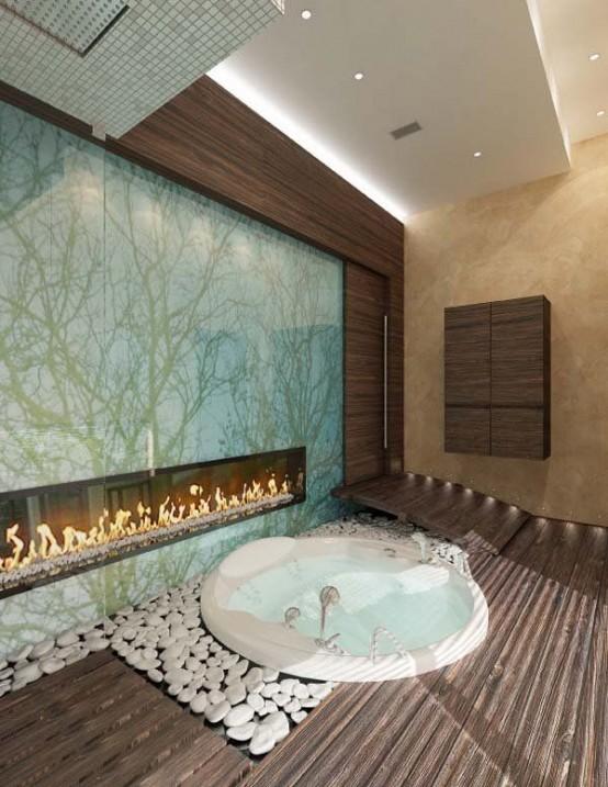 una vasca da bagno rotonda incassata con ciottoli bianchi intorno, con un ponte in legno e un caminetto incorporato per un maggiore relax