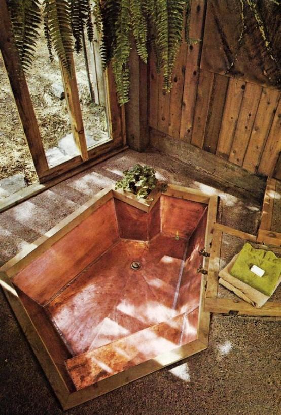un bagno naturale con pavimento in pietra, pareti in legno di pallet e una vasca asimmetrica rivestita di rame al suo interno