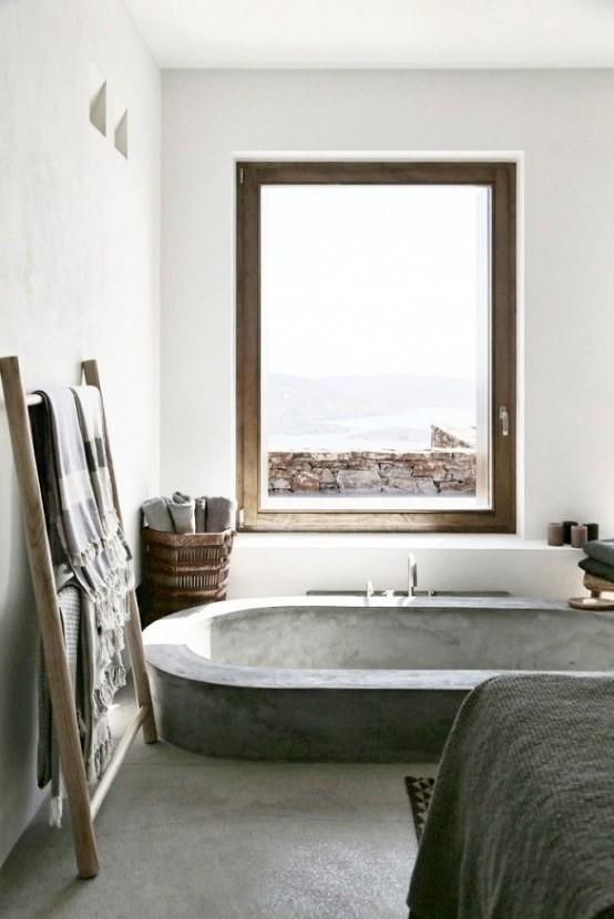 un bagno minimalista con cemento e pietra, con una vasca da bagno incassata in cemento, vista sul mare