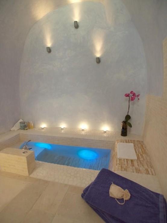 una vasca da bagno incassata in stile con una curva per una comoda inclinazione, luci e fiori in vaso per un'atmosfera