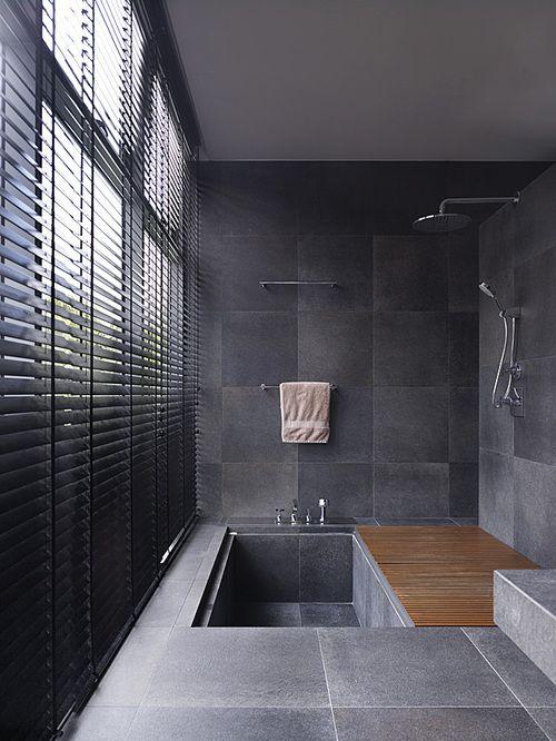 un bagno piastrellato minimalista con una vasca incassata piastrellata e un tappetino in legno è sorprendente per uno spazio contemporaneo