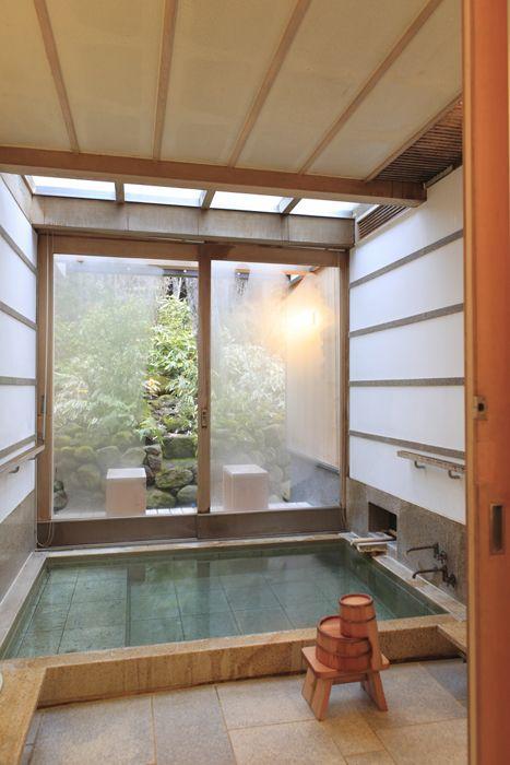una vasca incassata piastrellata in stile ofuro con sgabelli e una vista su un giardino giapponese attraverso le porte scorrevoli in vetro frontale