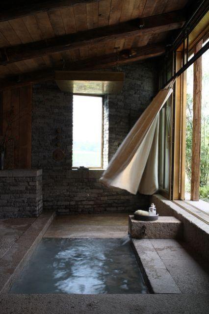 uno spazio esterno-interno fatto in pietra e cemento più una vasca da bagno incassata o una piscina a tuffo