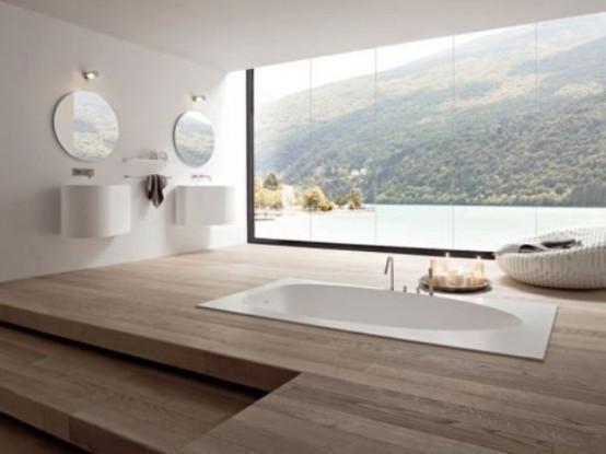 un ampio bagno minimalista con un elegante pavimento in legno e una vasca da bagno incassata oltre a una fantastica vista attraverso una finestra panoramica