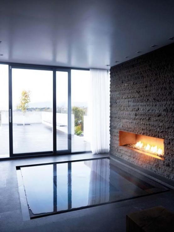 una grande vasca da bagno incassata con un muro di pietra finta e un caminetto è uno splendido spazio rilassante