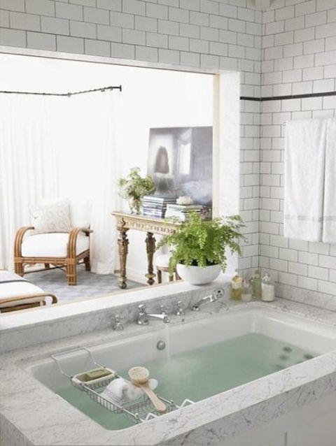 una vasca da bagno incassata rivestita di pietra neutra e con una finestra sulla camera da letto più alcune candele e una pianta in vaso