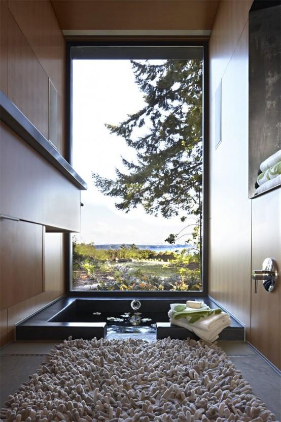 un batutb incassato con una vista stupenda grazie a una finestra panoramica e un tappeto molto soffice accanto