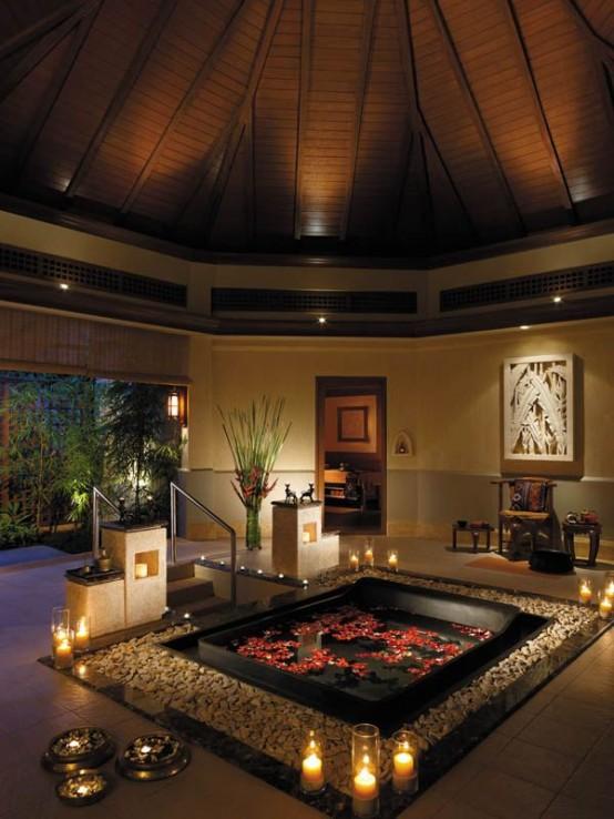 una vasca da bagno incassata con ciottoli e candele intorno, con petali e una scala per massimizzare il tuo comfort