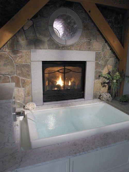 una vasca da bagno incassata da sogno con un camino con una cascata è uno spazio di balneazione molto rilassante