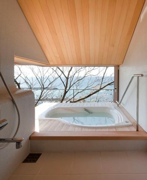 un bagno minimalista esterno-interno con vasca asimmetrica, vista e terrazza per godersi il più possibile il panorama