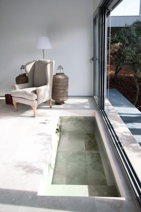 una vasca da bagno incassata minimalista proprio in camera da letto, con una porta scorrevole per rendere immediatamente esterno questo spazio