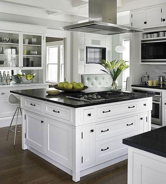 armadi bianchi di ispirazione vintage e una grande isola cucina al centro con top neri e hardware nero