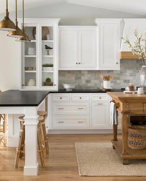 armadi bianchi di ispirazione vintage con piani neri e alzatina in piastrelle di marmo grigio per un'accogliente cucina da fattoria
