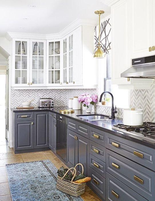 questa cucina grigia e bianca con piani di lavoro scuri presenta due tendenze in uno: due colori e piano di lavoro