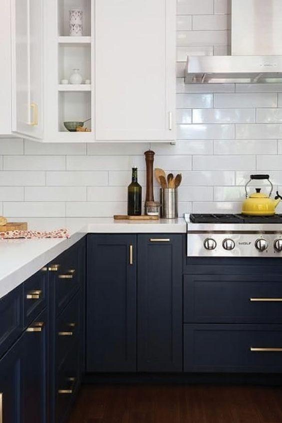 una cucina bicolore alla moda con armadi bianchi e neri, piani bianchi e hardware dorato più un backsplash in piastrelle bianche della metropolitana