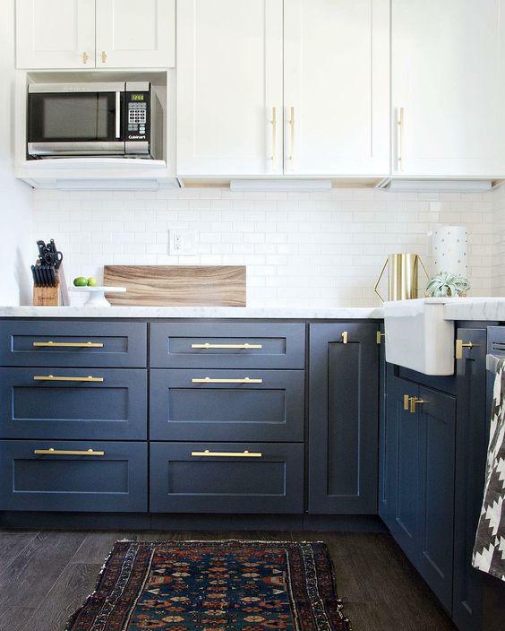 una cucina alla moda in due tonalità di blu e bianco con top bianchi e hardware dorato che gli conferiscono un aspetto più moderno