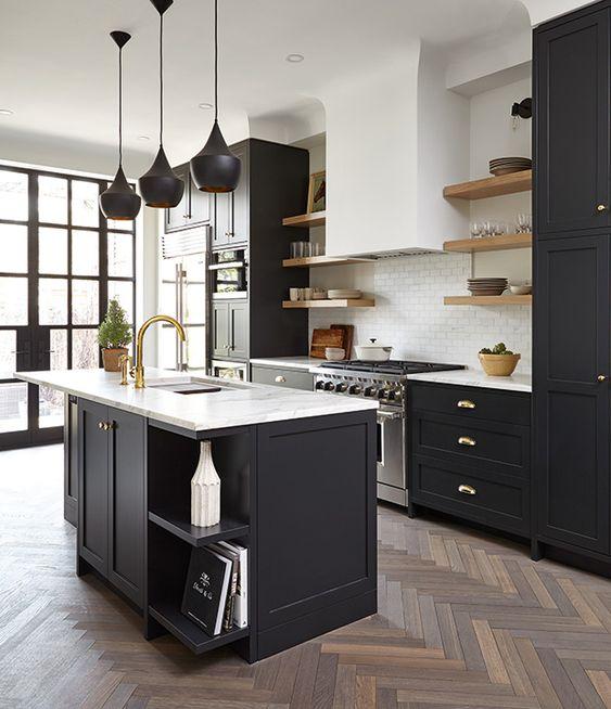 una moderna cucina da fattoria con armadi neri e piani in pietra bianca più hardware in ottone