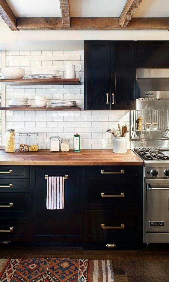 una cucina da fattoria con armadi neri, piano di lavoro neutri da macellaio e ferramenta in ottone