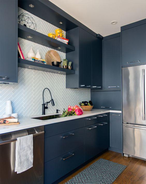 una cucina blu contemporanea con piani bianchi e un backsplash di piastrelle bianche rivestito con un motivo